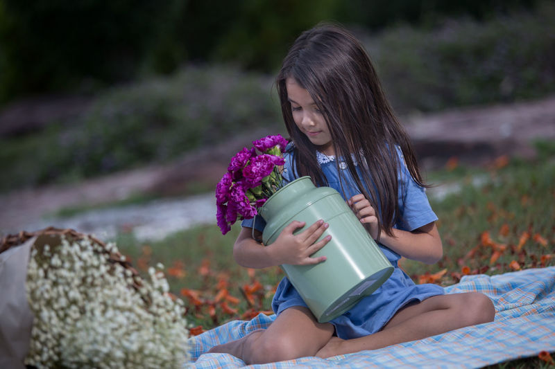 Cute Girl Holding Flowers In Container While Sitting On Blanket In Park