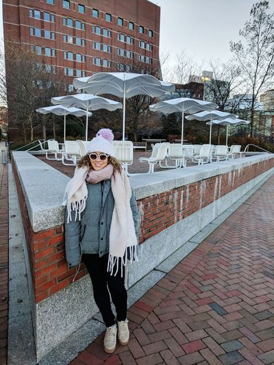 Portrait Of Young Woman By Retaining Wall Against Sidewalk Cafe