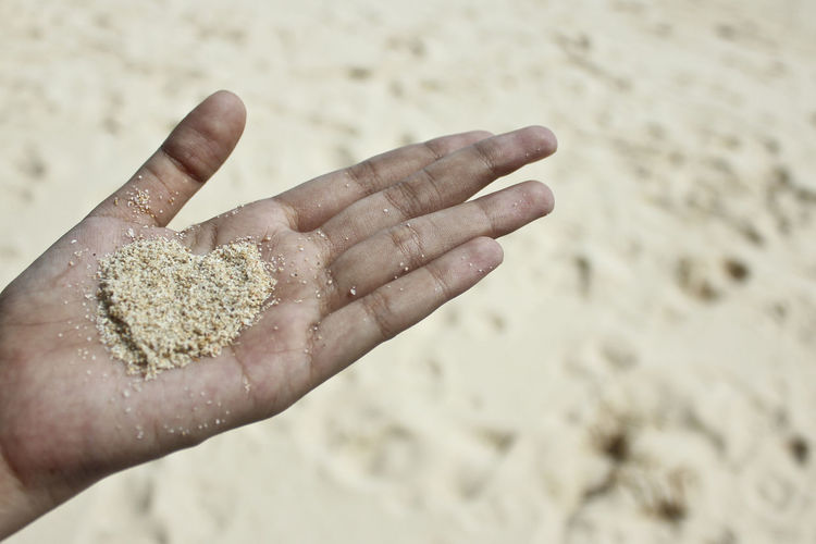 Cropped hand of woman holding heart shape sand
