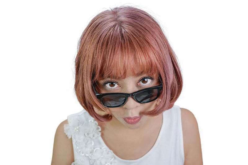 Surprised Asian woman with pink shot hair looking you above eyeglasses, isolated on white with clipping path. Beautiful Surprised Woman Clipping Path Cut Out Emotion Exited  Expression Eyeglasses  Female Headshot Isolated White Background Look Looking At Camera One Person People Portrait Shock Shot Hair  Studio Shot Surprise White Background Wonder Work Path Young Adult