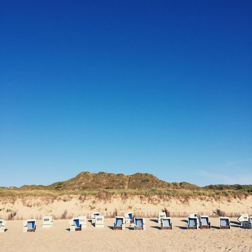 Panoramic view of sun loungers on beach against clear blue sky