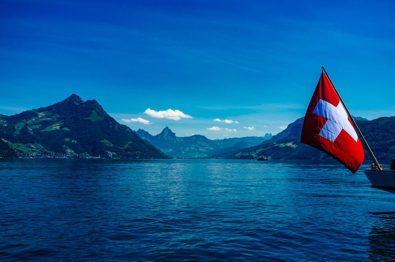 Swiss flag by river and mountains against sky