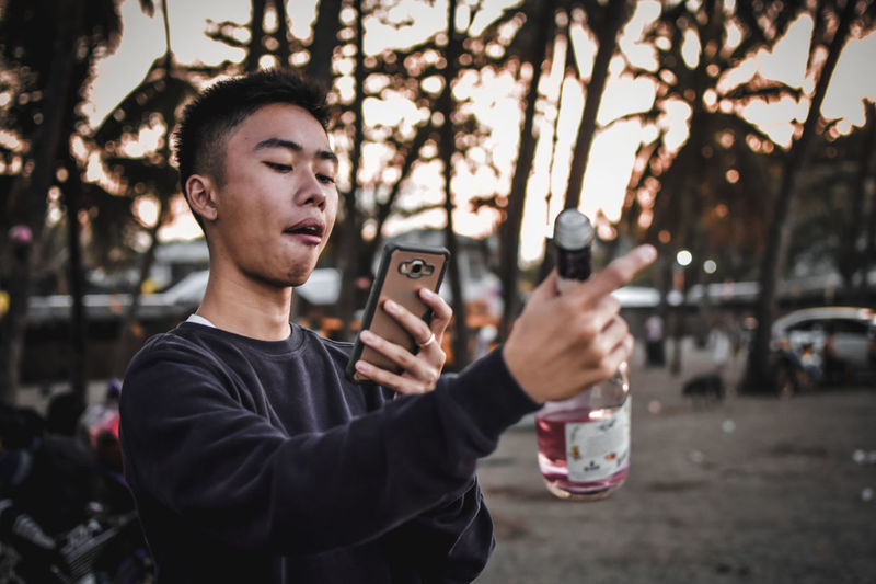 Young man photographing alcohol bottle outdoors