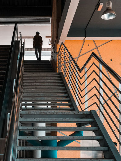 Low angle view of man walking up a staircase at the train station