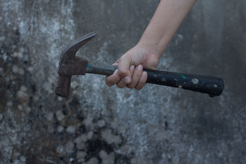 Cropped Hand Of Person Holding Hammer Against Wall