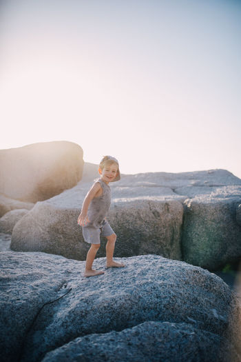 Portrait of cute smiling boy standing on rock against clear sky