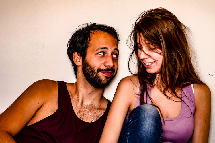 Portrait of happy young couple against wall