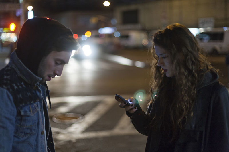 Woman using smart phone in city at night
