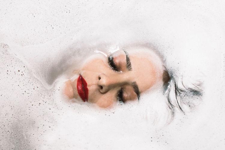 Portrait of woman lying down in bathroom