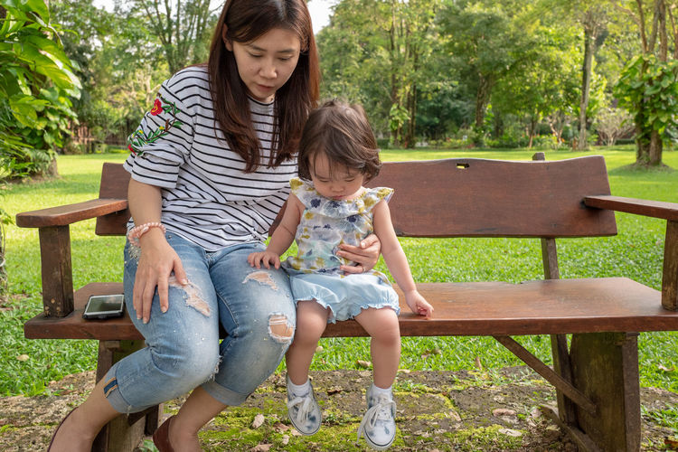 Adult Bench Bonding Care Casual Clothing Child Childhood Daughter Day Family Females Front View Full Length Girls Innocence Mother Outdoors Parent Park Bench Seat Sitting Togetherness Two People Women