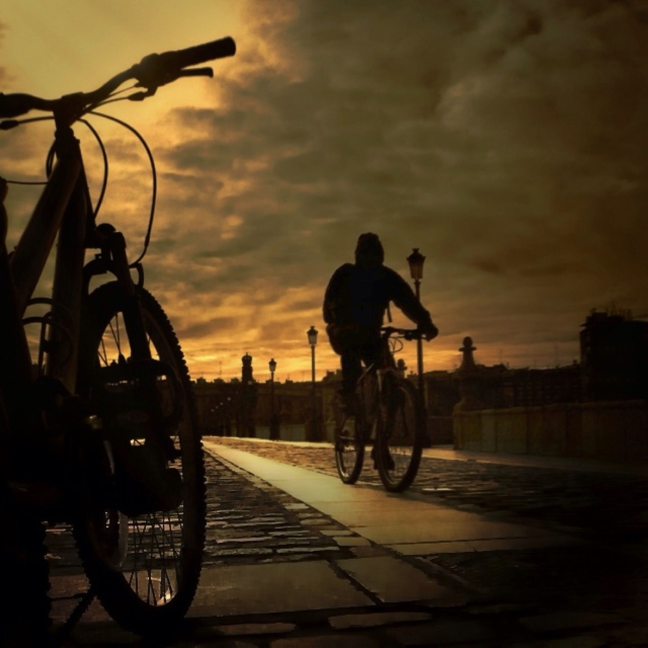 transportation, bicycle, mode of transport, land vehicle, riding, men, sunset, silhouette, cycling, sky, lifestyles, road, street, on the move, full length, leisure activity, cloud - sky, travel