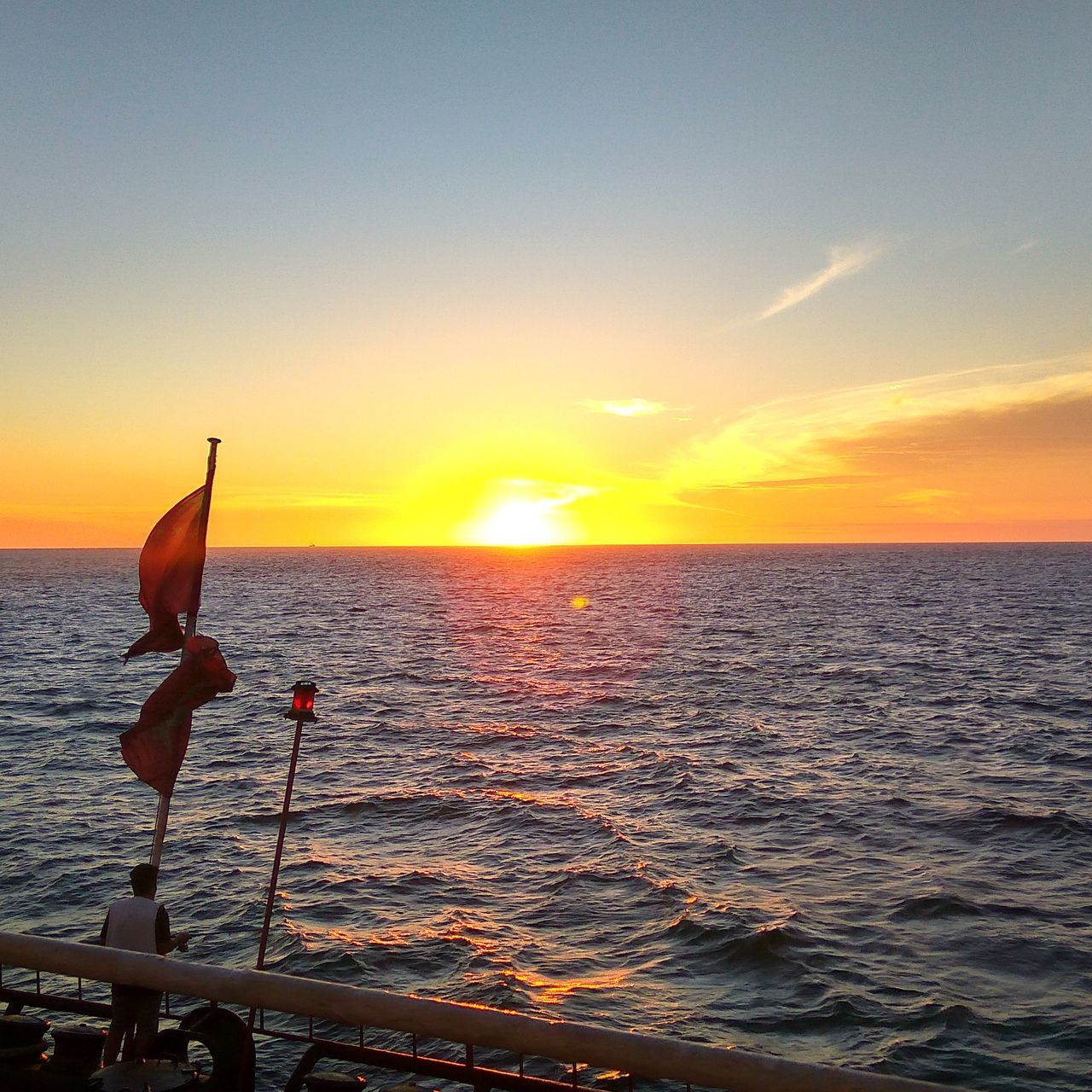 sunset, sea, water, horizon over water, beauty in nature, nature, scenics, orange color, tranquility, tranquil scene, sky, sun, outdoors, one person, weekend activities, fishing pole, vacations, men, nautical vessel, people