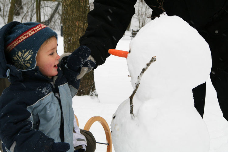 Midsection Of Parent With Boy Making Snowman During Winter
