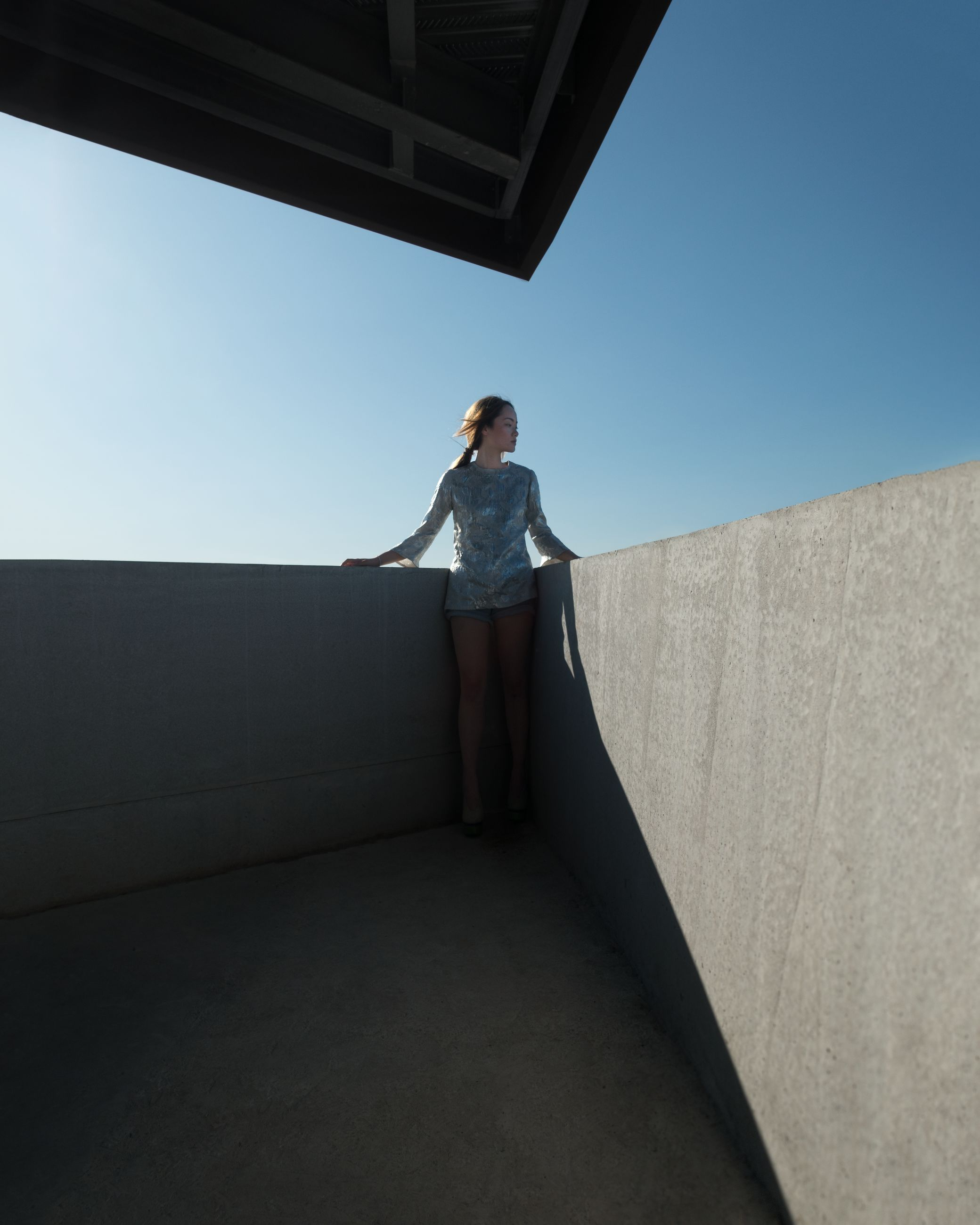 standing, real people, one person, lifestyles, sky, leisure activity, architecture, front view, wall - building feature, full length, young women, young adult, built structure, clear sky, low angle view, casual clothing, nature, sunlight, day, contemplation, teenager