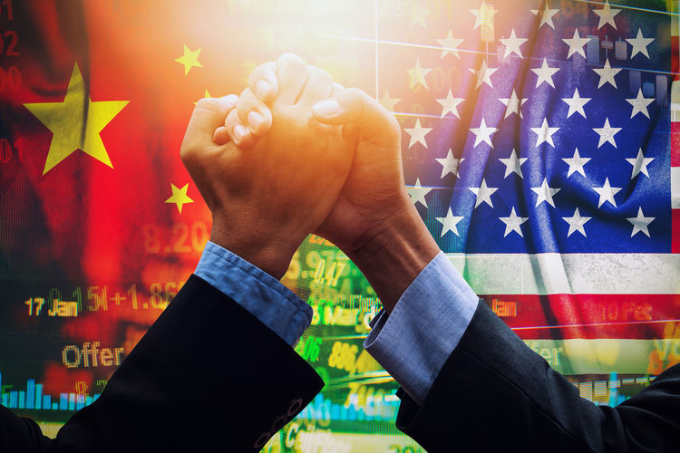 Business colleagues holding hands against chinese and american flag