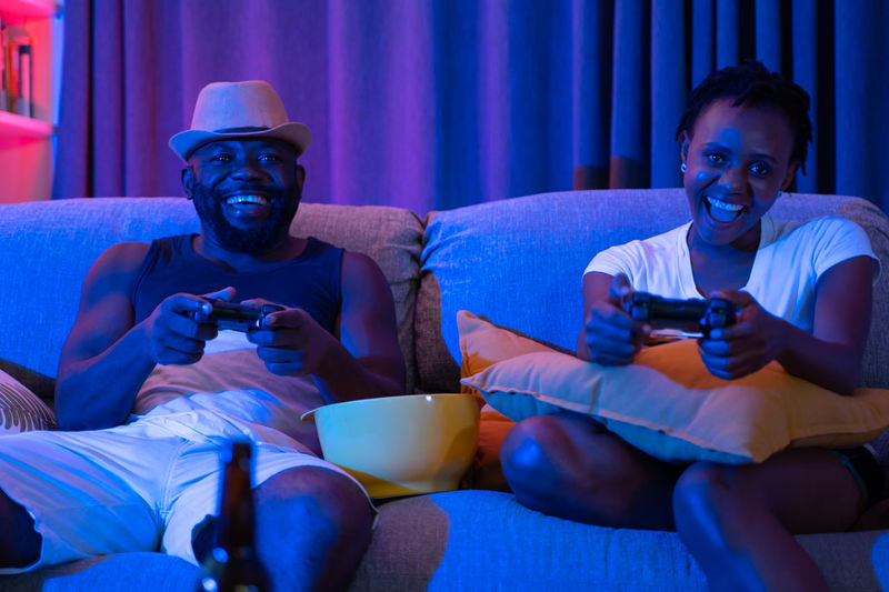 Happy African couple playing video games on console Couple Couple - Relationship Home House Love Togetherness Together Game Gaming Console Joystick African Happy Living Room Neon Arts Culture And Entertainment Sitting Sofa Men Three Quarter Length Leisure Activity Lifestyles Two People Looking Furniture Indoors  Front View Watching Young Adult Holding Males  Casual Clothing Relaxation Watching Tv Snack Video Games Games