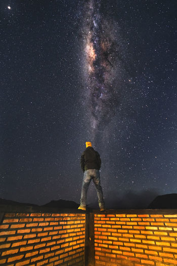 Rear view of man standing on brick wall against star field at night