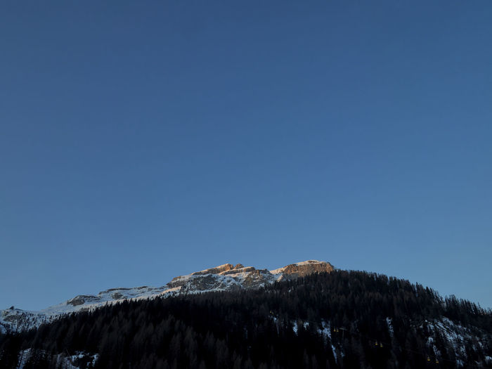 Low angle view of snowcapped mountain against clear blue sky at sunrise