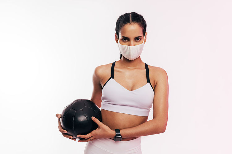 Portrait of young woman wearing mask with medicine ball against white background