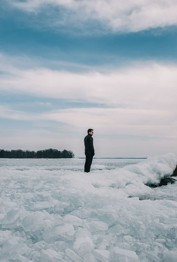 Man standing on snow field against sky