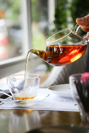 Close-up of hand pouring tea in glass