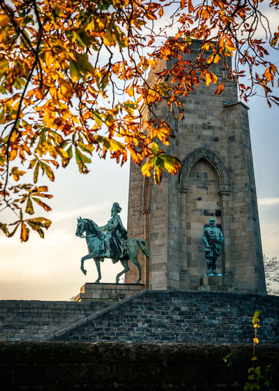 Low angle view of statue against sky during autumn