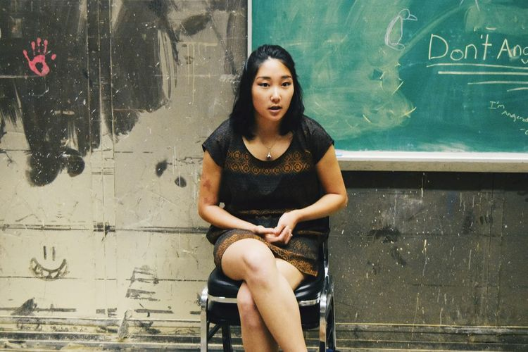Woman Sitting On Chair Against Chalkboard On Old Wall