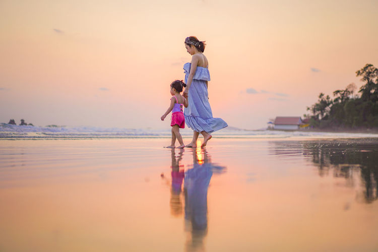 Mother with daughter walking at beach against sky during sunset