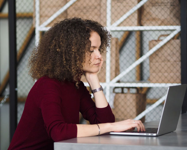 Portrait of a young beautiful serious woman with curly hair working in cafe on laptop.