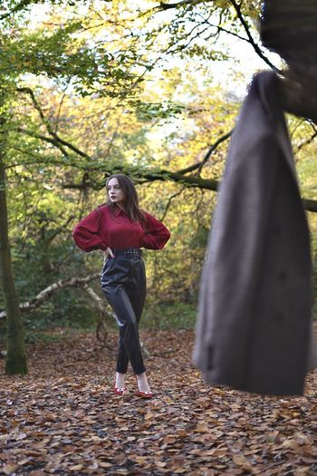Full length of woman with hands on hip standing in forest