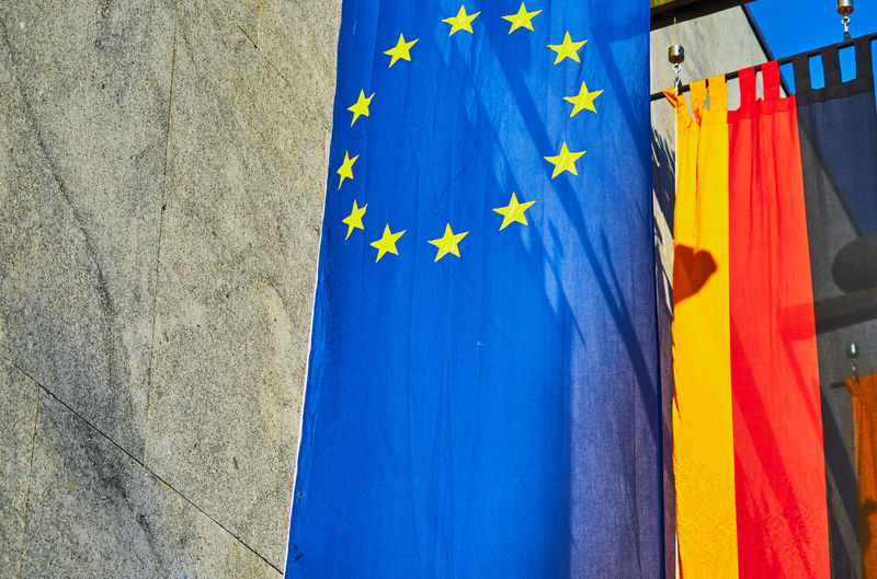 Close-up of flags hanging against blue sky