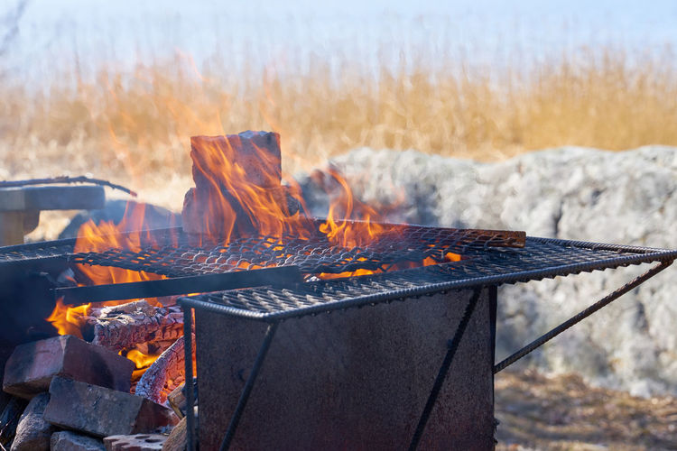 Fire in a rusty vintage grill outdoor on the beach of the sea.
