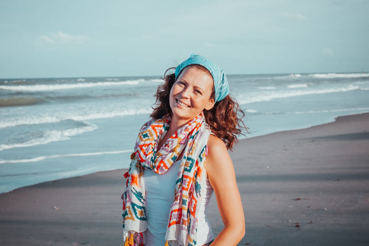 Portrait of charming woman enjoying beautiful seascape walking alone on the beach on summer day