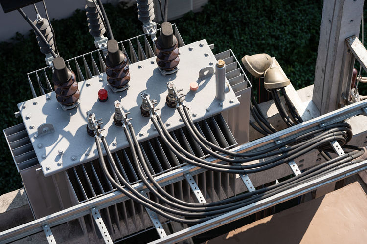 Top view of high voltage power transformer with electrical insulation in power substation.