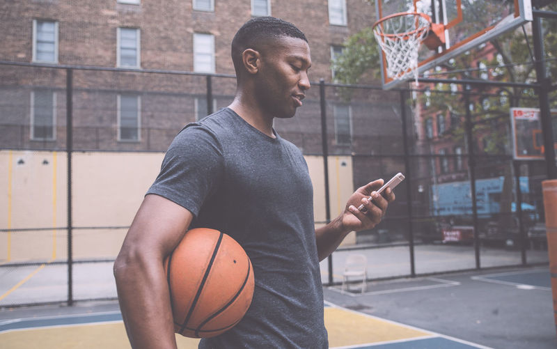 Young man using mobile phone while standing in basketball court