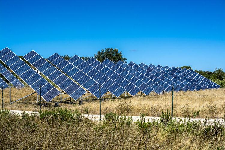 Solar panels on field against sky