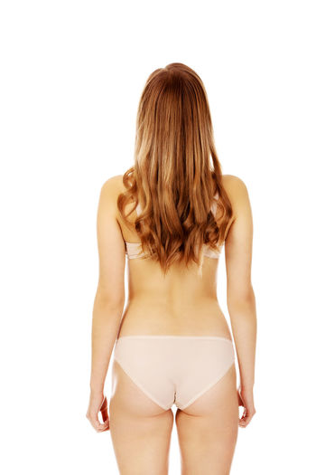 Rear view of woman wearing lingerie against white background