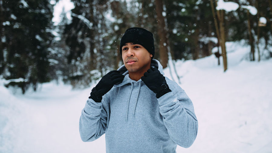 Young Man Standing On Snow Covered Field