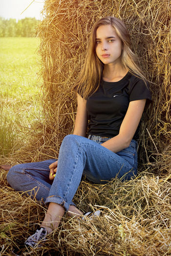 Portrait of young woman sitting on field