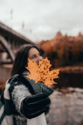 Close-up of woman holding maple leaf during autumn