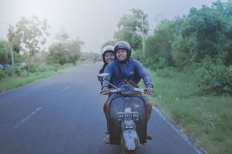 Portrait of young man riding motorcycle on road