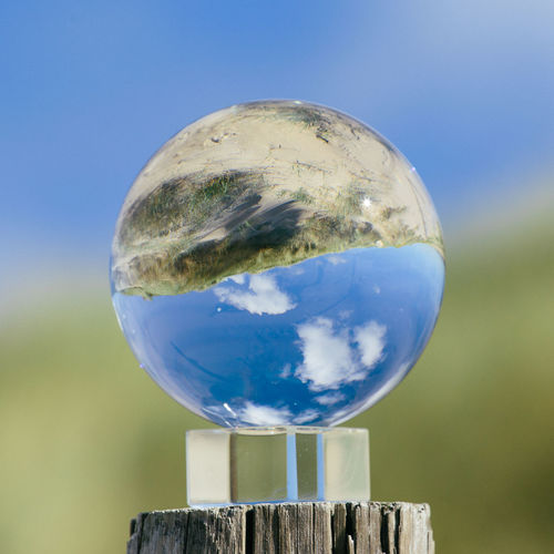 Close-up of crystal ball against blue sky