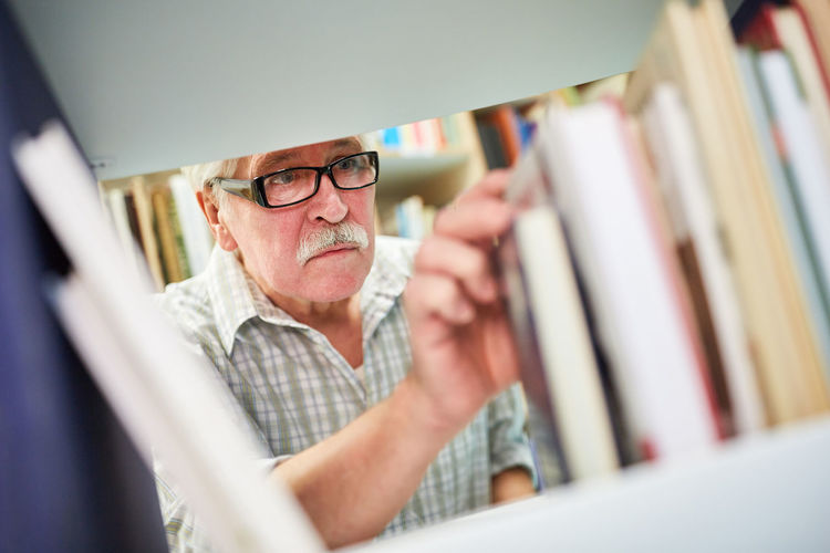 Low angle view of man choosing book in library