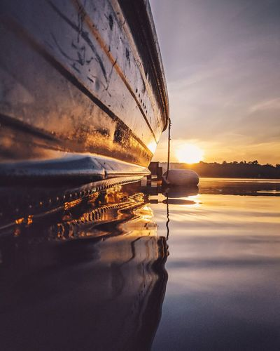 Rowboat moored on lake against sky during sunrise