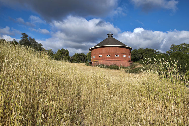 Round red barn Cloud - Sky Sky Built Structure Architecture Building Exterior Land Field Nature Grass Landscape No People Tranquil Scene Tree Outdoors Barn Red Color Wooden Historical Building Architecture Roof Windows
