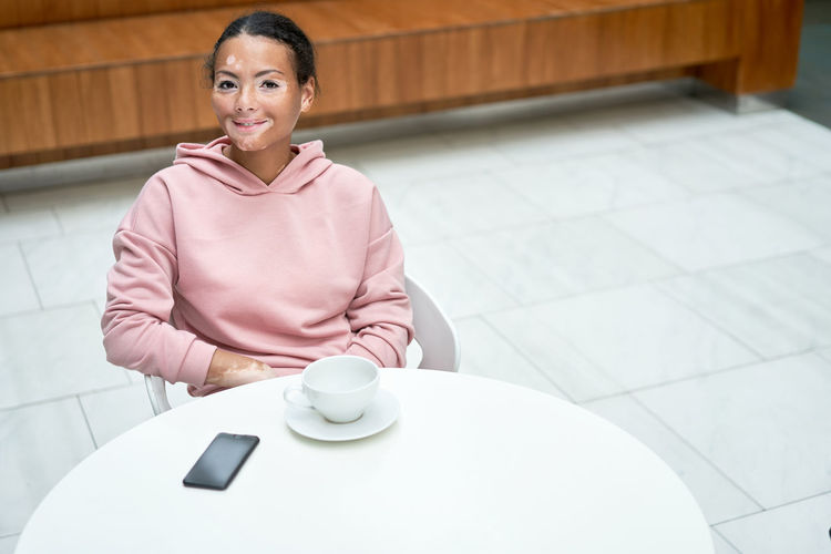 Portrait of a smiling young woman sitting on table