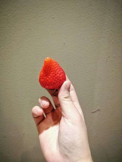 Midsection of person holding strawberry against wall