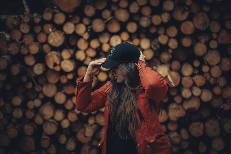 Close-up of woman wearing hat standing on wood