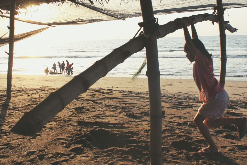 Girl swinging on bamboo structure at beach during sunset
