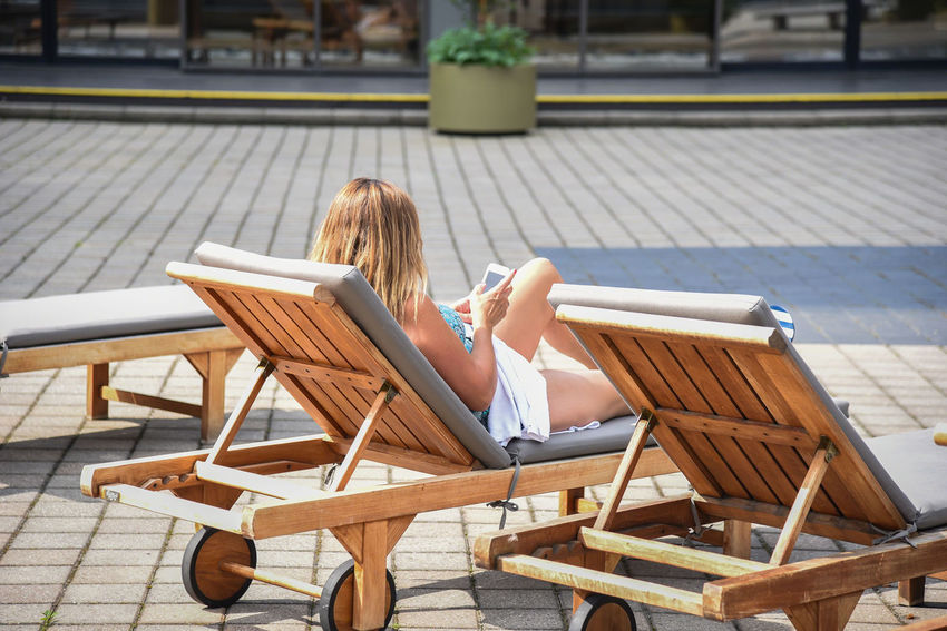 Woman checking phone on vacation while laying in chaise lounge chair Adult Chair Lifestyle Luxury Hotel Tanning Woman Blond Hair Chaise Day Deck Device Screen Female Leisure Activity Lifestyles Lounge One Person Outdoors Real People Relaxation Sitting Smartphone Sun Sun Bathing Teak Young Adult